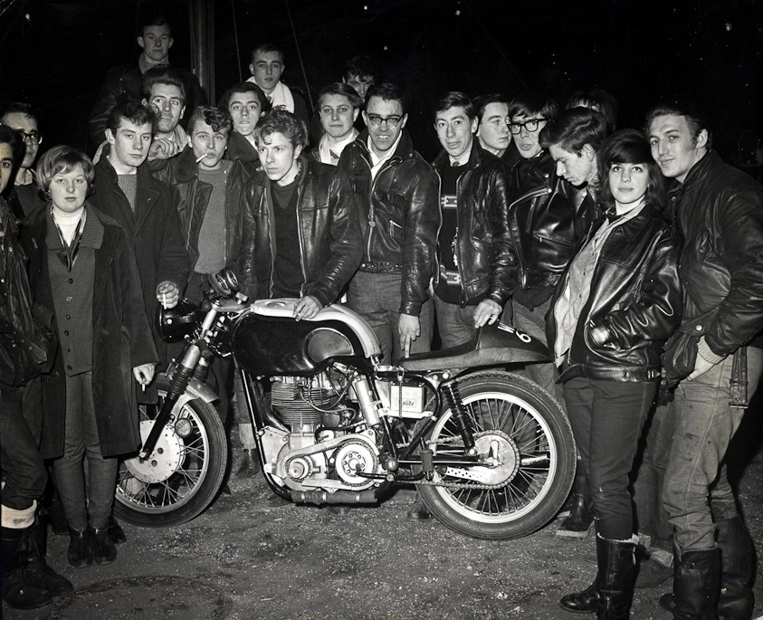 British teens stand around a cafe racer motorcycle circa 1960