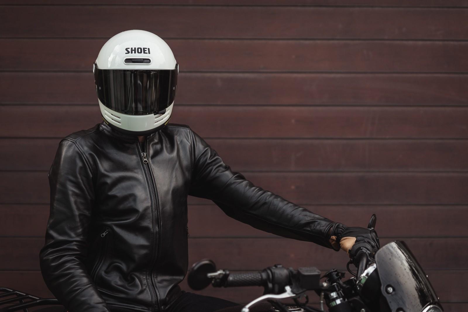 Person wearing Shoei Glamster helmet on motorcycle