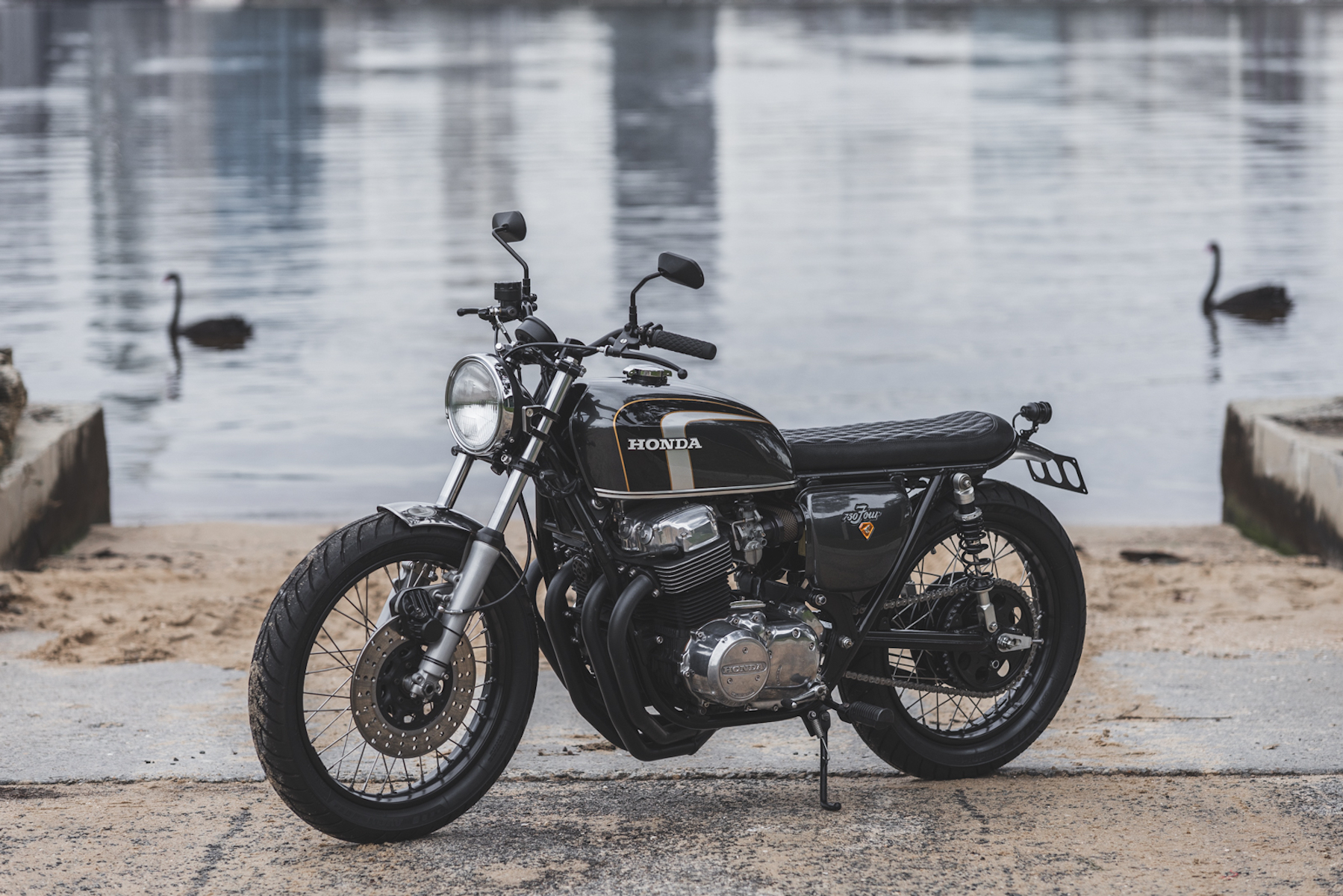 A side view of a Honda CB750 with Swans in the backround